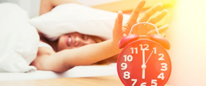 Beautiful young woman frowning in bed and holding hand on red alarm clock.